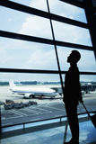 Silhouette of businessman waiting in the airport and looking out the window Royalty Free Stock Photo