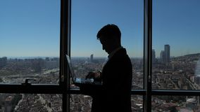 Silhouette of businessman is working on his laptop near the panoramic window with city view. Silhouette of businessman is working on his laptop in office. He is stock footage