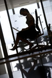 Silhouette of businesswoman sitting in office chair, using laptop, profile, surface level (tilt) Stock Image