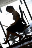 Silhouette of businesswoman sitting in office chair, using laptop, profile (tilt) Royalty Free Stock Photography