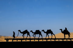 Silhouette of camel caravan. Silhouette of iron camel caravan in front of a window in desert Royalty Free Stock Images