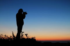 Silhouette cameraman against a sunset Royalty Free Stock Images