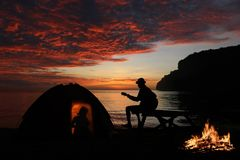 Couple camping with guitar and campfire on the beach Stock Images