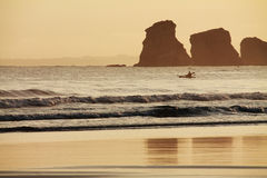 Silhouette of canoeist rowing and fishing in atlantic ocean by deux jumeaux in sunrise Royalty Free Stock Photo