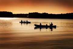 Silhouette of Canoers on Lake Stock Photo
