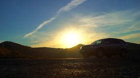 Silhouette of car traveling in mountains on gorizont at sunset light, sun lens flare, outdoors. country road. mountain stock video footage