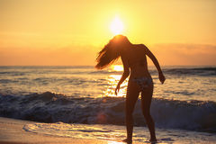 Silhouette of carefree woman on the beach Stock Photos
