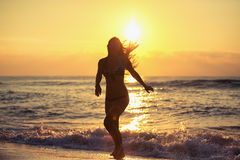 Silhouette of carefree woman on the beach Stock Images
