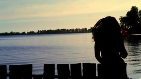 Silhouette of the carefree woman dancing at the beach during beautiful sunrise. vacation vitality healthy living concept