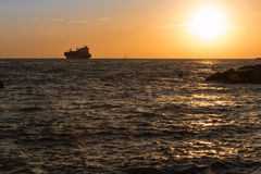 Silhouette of Cargo Boat in the Sea at Sunset Stock Photos