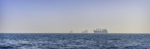 Silhouette of cargo ship in the ocean Royalty Free Stock Photo