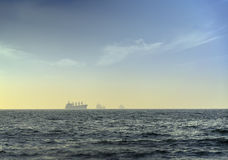 Silhouette of cargo ship in the ocean Stock Photo