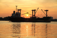 Silhouette of cargo ship in the river Royalty Free Stock Photos