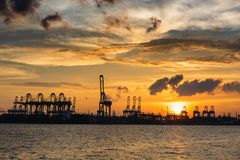Silhouette of cargo shipping terminal before sunset at Singapore stock images