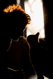 Silhouette of cat and girl ,. Silhouette of a beautiful cat and woman ,  Woman cuddling cat Stock Images