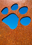Silhouette of a cat paw. In rusty metal wall Stock Images