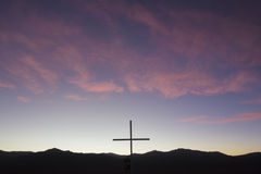 Silhouette of catholic cross in the mountain at sunset, Bolivia. Colorful purple sunset with the silhouette of a Christian cross located at the top of a mountain stock image
