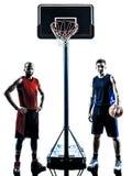 Silhouette caucasienne et africaine d'homme de joueurs de basket Photographie stock libre de droits