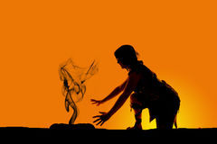 Silhouette of a cave woman kneel by fire Royalty Free Stock Photos