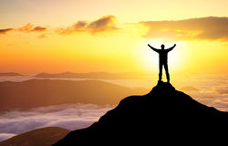 Silhouette of a champion. On mountain peak. Active life concept stock image