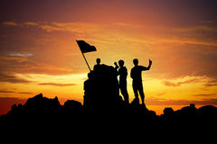 Silhouette of a champion on mountain peak at sunset. Stock Image