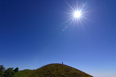 Silhouette of a champion on mountain top with sun star. Stock Images