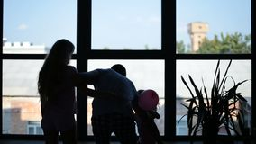 Silhouette of happy family embracing near window stock video