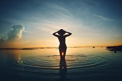Silhouette of woman in the ocean meeting sunrise. Silhouette of cheerful woman in the ocean meeting sunrise Stock Photo