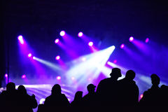 Silhouette of cheering crowd at a concert. Colorful bright stage lights in the background Royalty Free Stock Images