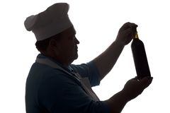 Silhouette of a chef looking at a bottle of wine and thinking on a white isolated background, profile of a male face in a cook hat royalty free stock photos