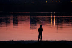 A silhouette of a child on a background of the river in the evening at sunset stock photography