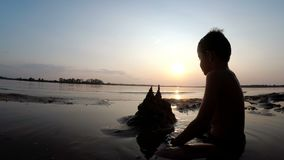 Silhouette of a Child on the Beach Building a Sand Castle at Sunset. Happy little boy sitting on the river bank and plays with sand. Summer vacation stock video footage