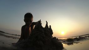 Silhouette of a Child on the Beach Building a Sand Castle at Sunset. Happy little boy sitting on the river bank and plays with sand. Summer vacation stock video