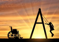 Silhouette of a child disabled girl on a swing next to a wheelchair on a sunset background. Concept of children with disabilities and their leisure stock image