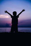 Silhouette of child enjoying the view at riverside. Cool colors Stock Photography