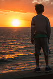 Silhouette of a Child in Front of Sea at Sunset Royalty Free Stock Photos