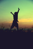 Silhouette of child jumping against sunset. Boy enjoying the vie Royalty Free Stock Images