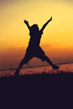 Silhouette of child jumping against sunset. Boy enjoying the vie Stock Image