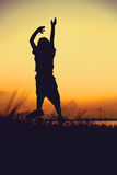 Silhouette of child jumping against sunset. Boy enjoying the vie Stock Images