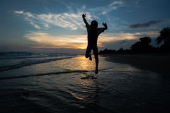 Silhouette of child jumping on the beach Royalty Free Stock Images