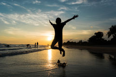 Silhouette of child jumping on the beach Stock Photos