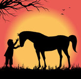 Silhouette of child petting a horse Royalty Free Stock Photos