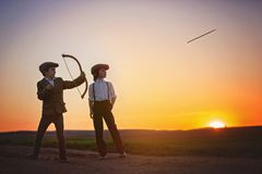 Silhouette of child playing with bow and arrows, archery shoots royalty free stock image