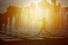 Silhouette of a child playing with a spray of a fountain on a hot summer day. Royalty Free Stock Photo