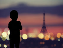 Silhouette of a child at window with Silhouette of Eiffel tower at Paris Royalty Free Stock Photography