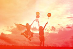 Silhouette children with balloon. At sunset Royalty Free Stock Photos