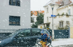 Silhouette of children crossing street on a snowy day diver. Silhouette of child kid on bike crossing street on a snowy day - senn by the driver point ov view royalty free stock photography