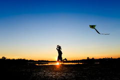 Silhouette of children flying a kite at sunset stock photography