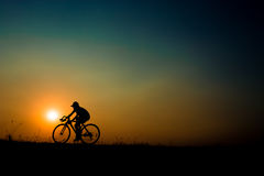 Silhouette children. Silhouette of girl at the sunset time on meadow riding a bike to the sun. Have background of a beauty yellow and blue sky and white of a sun Stock Photo