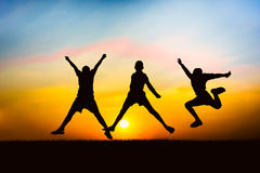 Silhouette of a children jumping. Silhouette of children jumping in meadow on sunset background Stock Photos